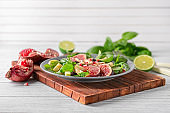 Plate with delicious fig salad on wooden table