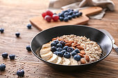 Tasty oatmeal with banana slices, blueberries and almonds on wooden table