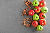 Fresh apples and cinnamon sticks on grey background