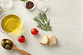 Composition with olive oil and different products on wooden table