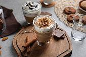 Glass of tasty aromatic latte on wooden board