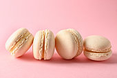 Fresh tasty macaroons on color background