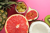 Different tropical fruits on color background
