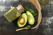 Flat lay composition with avocado and natural cosmetic for hair on grunge background