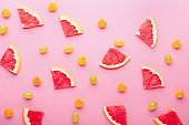 Slices of grapefruit, grapes and cape gooseberries on color background