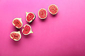 Ripe cut figs on color background