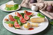 Plate with ripe figs and cheese on color table