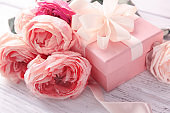 Beautiful flowers and gift box on wooden background, closeup