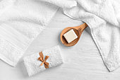Clean soft towels and spoon with soap on light wooden table