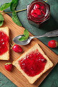 Board with slices of bread and delicious strawberry jam on green table
