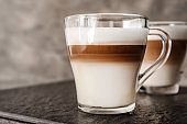 Glass cups of tasty aromatic latte on slate plate
