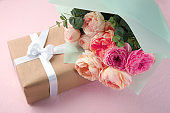 Beautiful flowers and gift box on color background