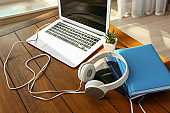 Modern headphones, laptop and notebooks on wooden table