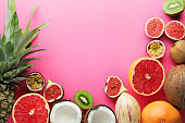 Summer composition with tropical fruits on color background