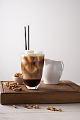 Glass of tasty cold coffee on wooden board