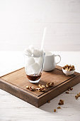 Glass of tasty coffee with ice cubes and walnuts on wooden board