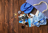 Bag with passport, camera and beach accessories on wooden background