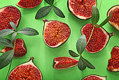 Fresh ripe figs and green leaves on color background, flat lay