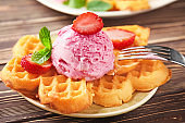 Delicious waffles with ice cream and strawberry on plate