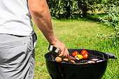 Man cooking tasty vegetables on barbecue grill outdoors