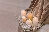 Tray with burning candles and cotton flowers on floor