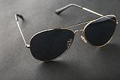 Stylish sunglasses on black background