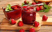 Glass jar and bowl with delicious strawberry jam on wooden table