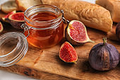 Fresh ripe figs with jar of honey on wooden board
