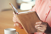 Young woman reading book in cafe, closeup