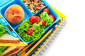 Lunch box with appetizing food and stationery on white background