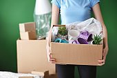 Woman with packed carton box indoors. Moving house concept