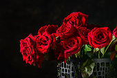 Vase with beautiful bouquet of red roses on dark background