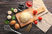 Wooden board with raw dough  and ingredients for pizza on table