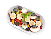 Plate with delicious fruit salad on white background