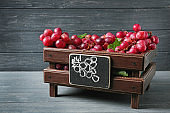 Wooden box with red grapes on table