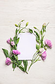 Beautiful eustoma flowers with blank card on white wooden background