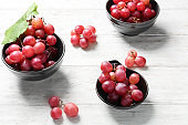 Bowls with red grapes on wooden table
