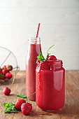 Glass jar and bottle with strawberry smoothie on wooden table