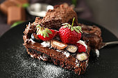Delicious chocolate cake with berries on plate, closeup
