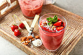 Glass with strawberry smoothie on wicker tray