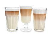 Glasses of tasty aromatic latte on white background