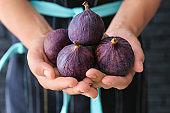 Woman holding fresh ripe figs, closeup