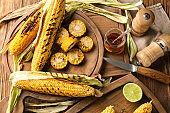 Tasty grilled corn cobs on wooden table