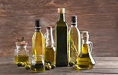 Glassware with olive oil on wooden background