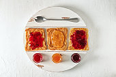 Delicious toasts with various sweet jams on white textured background