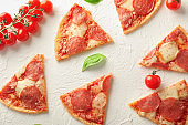 Pieces of pepperoni pizza on light background