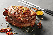 Slate plate with tasty grilled steaks and spices on grey background