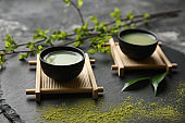 Bowls of fresh matcha tea on slate plate