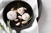 Frying pan with fresh garlic and rosemary on table