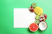 Composition with various delicious exotic fruits and blank card on color background